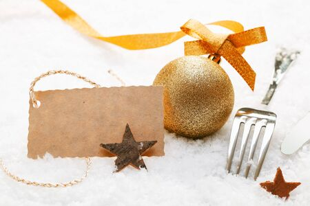 wintry: Festive place setting with Christmas decorations and silver cutlery in fresh winter snow with a decorative blank gift tag Stock Photo