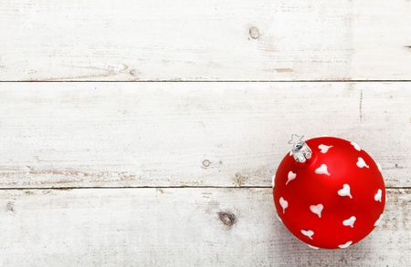 A vivid red bauble dotted with white hearts suitable as a Christmas or Valentines decoration on a background of white wooden boards with copyspace photo