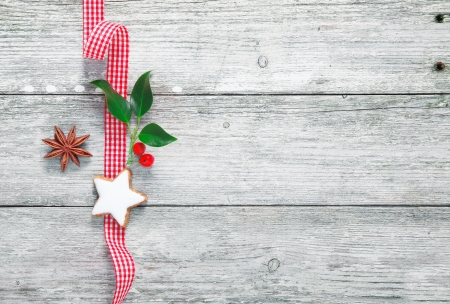 white christmas: Vintage Christmas decoration on old wooden boards with holly and a star on a fresh red and white checked ribbon with copyspace