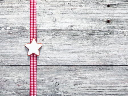 woodgrain: Christmas star biscuit and festive ribbon on grungy white weathered wooden boards with woodgrain texture and copyspace