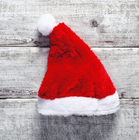 christmass: Red Santa Claus hat lying on rustic weathered wooden boards for a country Christmas greeting