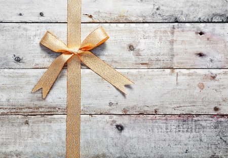 Decorative golden bow and ribbon on old rustic wooden boards with woodgrain copyspace for your Christmas, birthday or anniversary message Stock Photo