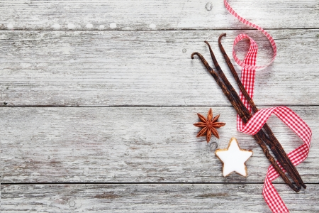 advent: Vintage Christmas spice background with a fresh checked ribbon twirled around vanilla pods and star anise on weather textured wooden boards with copyspace Stock Photo