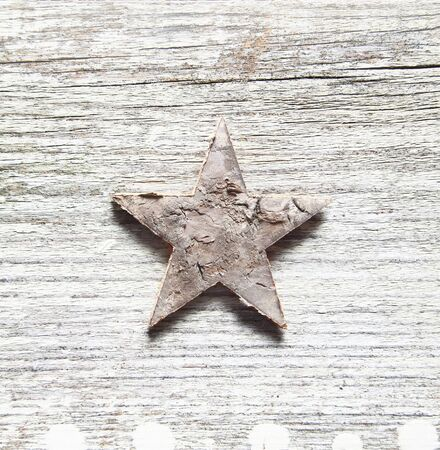 Grungy Christma background with a damaged peeling star centred on old textured cracked and weatherworn wood photo