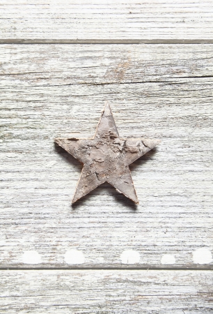 centred: Old grungy Christmas star centred vertically on weathered planks with woodgrain and copyspace Stock Photo