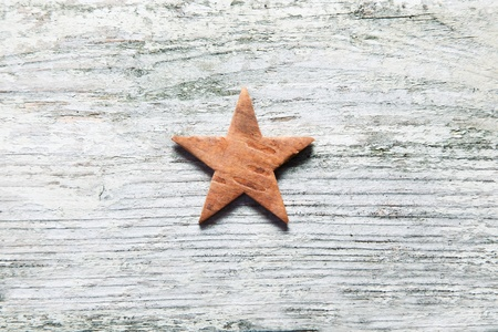 centred: Rustic Christmas star centred on grungy old white weathered wooden boards with grain texture and copyspace Stock Photo