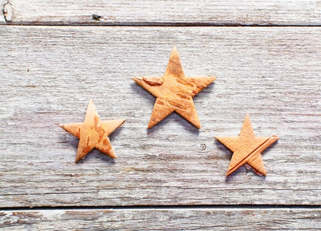 Three decorative Christmas stars on grungy weathered wooden boards with copyspace photo