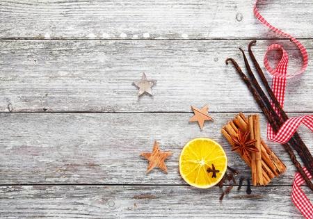 dried spice: Colorido conjunto de especias de Navidad decorativos con un fresco rojo y blanco cinta giraba sobre un fondo de textura grungy madera desgastada blanco