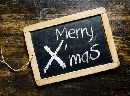Merry Xmas greeting handwritten on a small slate chalkboard lying on old textured wooden boards photo