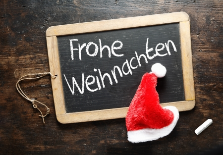 Frohe Weihnachten Christmas greeting handwritten in German on a chalkboard slate with a colourful red Santa hat photo