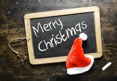 merry christmas text: Manuscrito Merry Christmas greeting en una pizarra peque�a con un mullido sombrero rojo de Santa en un fondo de madera Foto de archivo