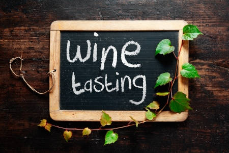 Handwritten decorative Wine tasting sign on a small rustic slate chalkboard Stock Photo