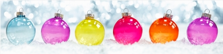 Colourful translucent Christmas baubles arranged in a row in snow against sparkling party ligts suitable as a banner or border Stock Photo