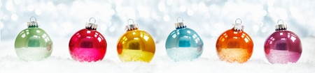 header image: Beautiful shiny Christmas ball banner arranged in a row on fresh white winter snow with a backdrop of sparkling lights