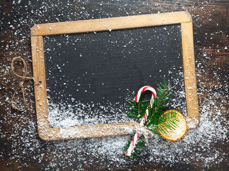 seasonal greetings: Blank rustic Christmas chalkboard slate with scattered snow and a colourful striped candy cane ready for your seasonal greetings