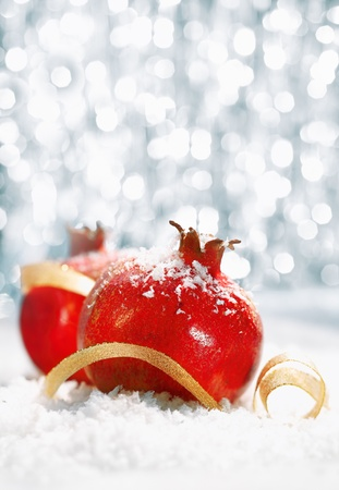 Red Christmas pomegranates in a bed of wintery snow with a gold ribbon and a bokeh of festive twinkling lights with copyspace for your seasonal greeting photo