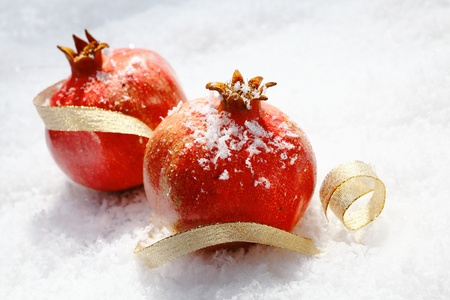 Vivid red Christmas pomegranates dusted with snowflakes lying in fresh winter snow with a decorative gold ribbon photo
