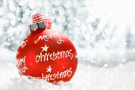 Beautiful atmospheric Merry Christmas greeting card with a red decorated bauble bearing the words Merry Christmas photo