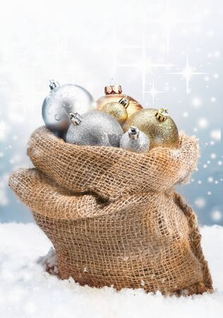 Winter Christmas baubles piled high in a rustic burlap bag nestled in fresh snow with a backdrop of twinkling stars on falling snowflakes photo