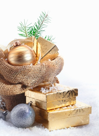 christmas ground: Rustic Christmas gift background with decorative baubles and golden gifts spilling out of a simple hessian sack onto the snowcovered ground with copyspace Stock Photo