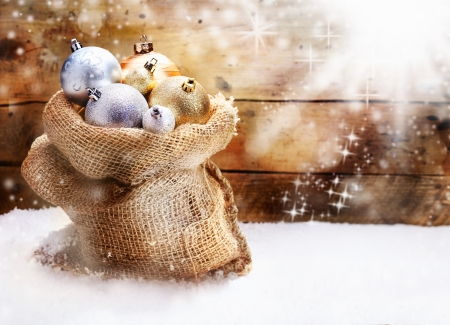 twinkling: Hessian sack filled to overflowing with gold and silver Christmas baubles resting on snow in front of a rustic wooden wall with twinkling snowflakes and copyspace