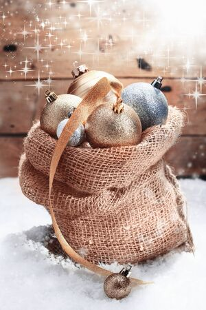 Decorative Christmas baubles piled high in a hessian bag on winter snow and decorated with a gold ribbon amidst dancing twinkling sunlight over a wooden wall Stock Photo - 16101492