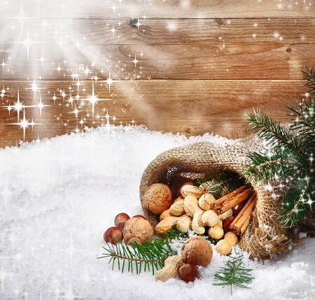 Festive christmas nuts and spices tumbling from a burlap bag onto fresh winter snow with sunlight catching twinkling falling snowflakes and copysapce photo