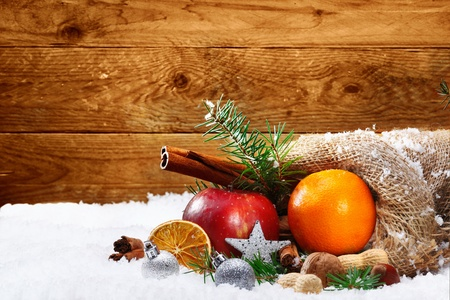 fruit plate: Artistic Christmas still life of colourful fruit and spices spilling out of a rustic burlap bag onto winter snow with a wooden board background and copyspace