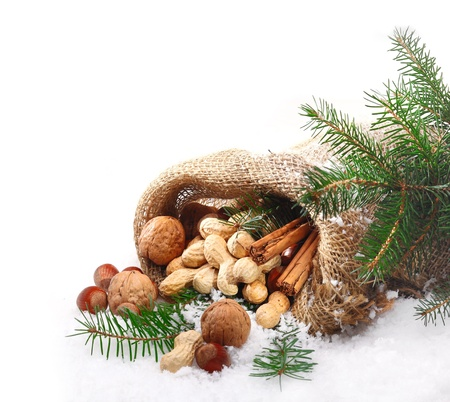 hessian bag: An assortment of traditional Christmas nuts spilling out of a hessian bag onto fresh winter snow with pine foliage and copyspace for your seasonal greeting