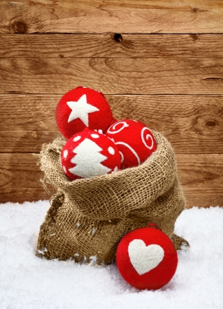 christamas: Beautiful red handcrafted Christmas decorations with traditional shapes outlined on fabric baubles spilling out of a hessian sack onto fresh snow with a timber background Stock Photo
