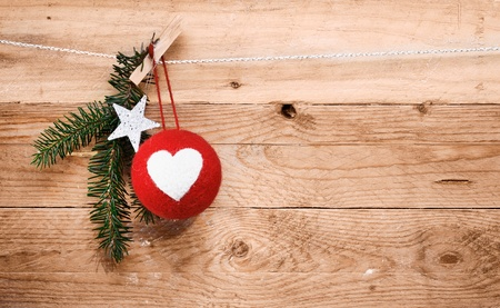 Country Christmas decorations with a red handcrafted fabric bauble decorated with a heart, a star and sprig of pine  Stock Photo - 16101555
