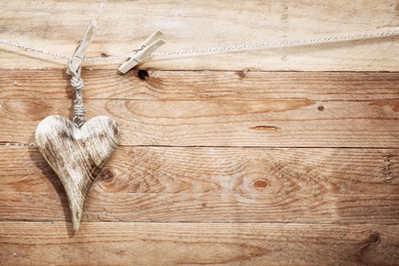 Beautiful romantic rustic wooden heart with an elongated shape hanging from a string by a clothespeg  photo