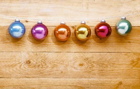 String of colourful shiny multicoloured Christmas baubles hanging from a line against a timber background  photo