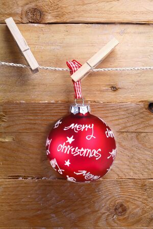 Colourful red merry Christmas bauble with a written greeting hanging from a line by a clothespeg over rustic rough wooden boards photo
