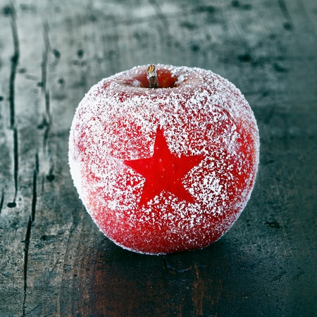 Decorative fresh ripe red Christmas apple frosted with a star pattern on an old vintage wooden table top, closeup in square format photo