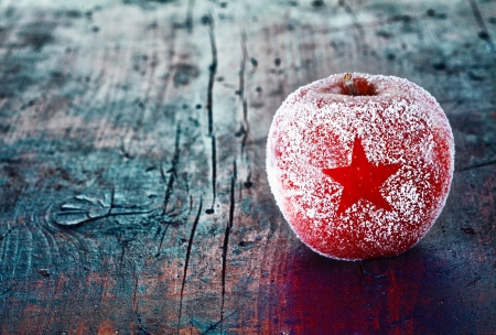apple christmas: Frosted Christmas apple with a simple star decoration on an aged vintage wooden table with copyspace for your traditional seasonal greeting