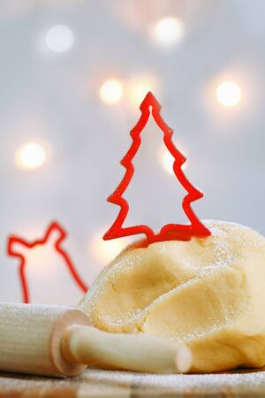 bickie: A red cookie cutter in the shape of a Christmas tree tops a freshly made mound of pastry dough while preparing Christmas cookies
