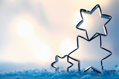 Three festive star cookie cutters balanced on blue wintery snow crystals outlined against soft muted lights with copyspace for your Christmas greeting photo
