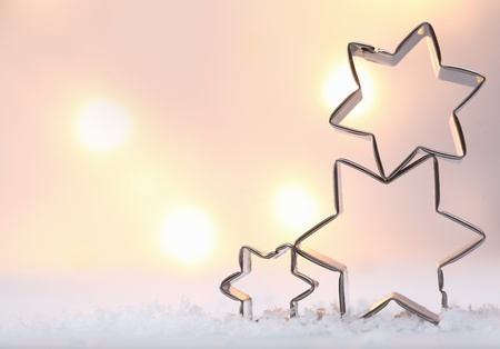 cookie cutter: Atmospheric Christmas star background with three metal star cookie cutters balanced on top of each other on snow against a soft moody bokeh of glowing lights with copyspace