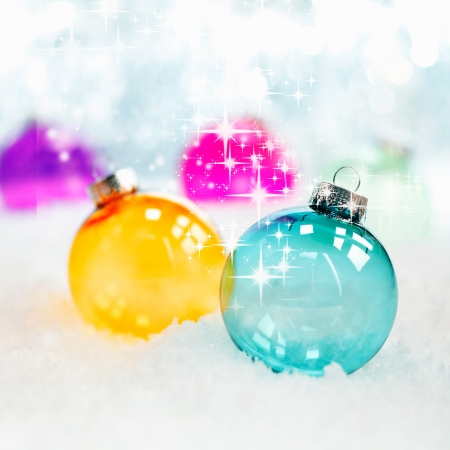 holiday season: Sparkling twinkling colourful translucent glass Christmas baubles in fresh winter snow with bokeh of soft white lights, square format Stock Photo