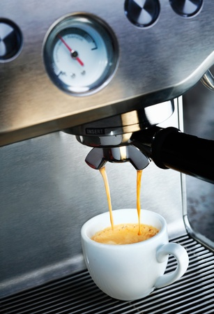 dispensing: Automatic filter coffee machine dispensing a cup of delicious hot frothy aromatic coffee into a white ceramic cup in a catering and hospitality background Stock Photo