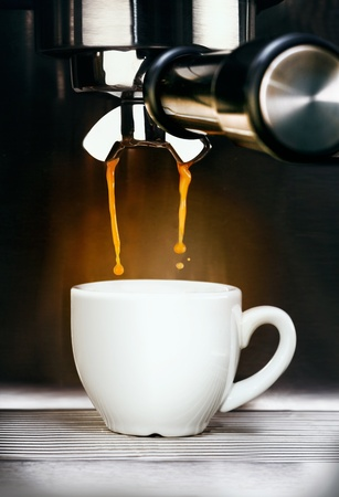 Closeup of a professional stainless steel coffee machine pouring freshly brewed aromatic espresso coffee into a plain white ceramic cup photo