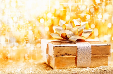 A luxury gold Christmas gift tied with an ornamental bow against a golden bokeh of sparkling festive lights with copyspace for your seasonal greeting photo