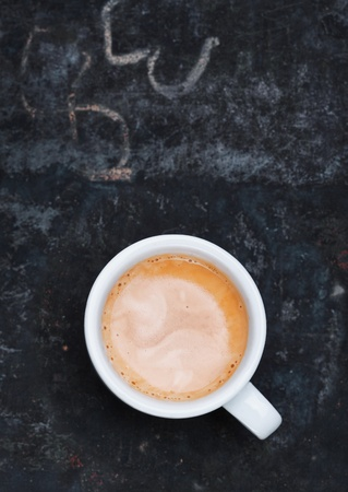cofee cup: Overhead view of an aromatic frothy cup of freshly brewed cappuccino standing on a grungy old blackboard slate with chalk scribblings and copyspace