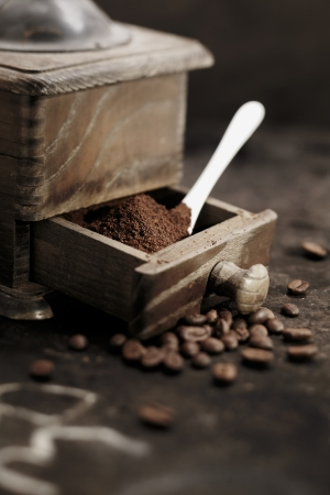 country kitchen: Pile of fresh ground coffee grains in the open drawer of an old rustic wooden coffee grinder with a measuring spoon in a country kitchen