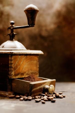 molinillo: Primer plano detalle de un molinillo de café de la vendimia con los granos que desbordan el cajón abierto. Neutral tono marrones antiguo vigor.