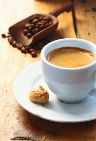 Strong aromatic espresso coffee served in a small cup with a macaroon on the side and a scoop of coffee beans in the background