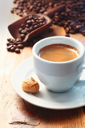 frothy: Tazza di mattina di caff� espresso schiumoso su un tavolo di legno fatto con chicchi di caff� freschi torrefatto macinato visto sullo sfondo fuoriuscita da uno scoop