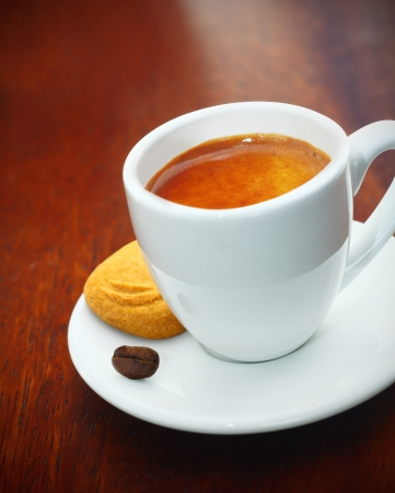 time table: Cup of freshly brewed frothy espresso coffee served with a crisp golden biscuit and single coffee bean on a dark wood table Stock Photo