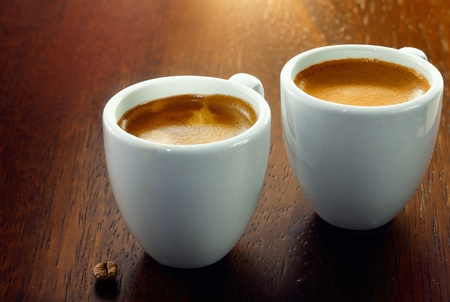 coffees: Two espresso coffees in small white cups,with a single coffee bean resting on the wood background Stock Photo
